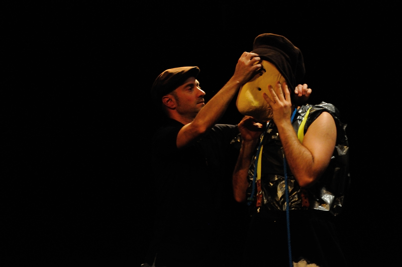 photo of the Larven show - Patrick Forian adjusts a mask of a actor